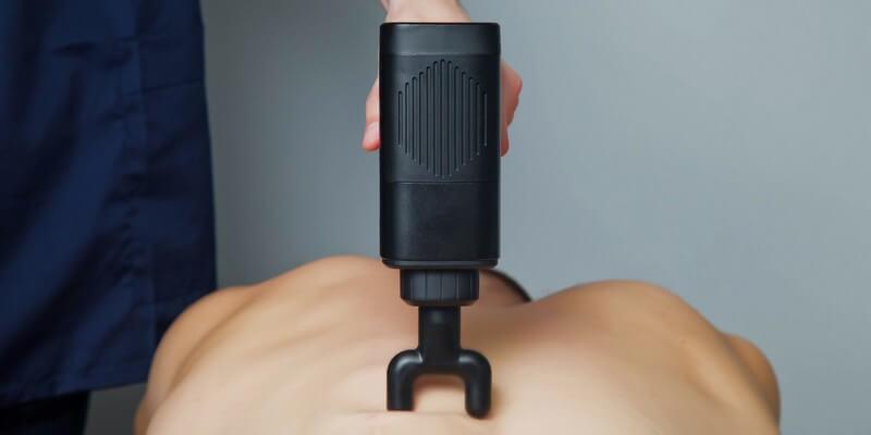 Homme qui utilise un pistolet de massage